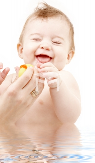 laughing baby boy in water playing with rubber duck