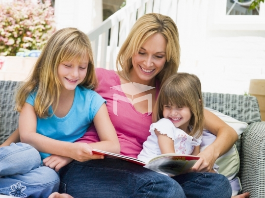 Woman and two young girls sitting on patio reading book smiling