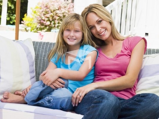 Woman and young girl sitting on patio smiling
