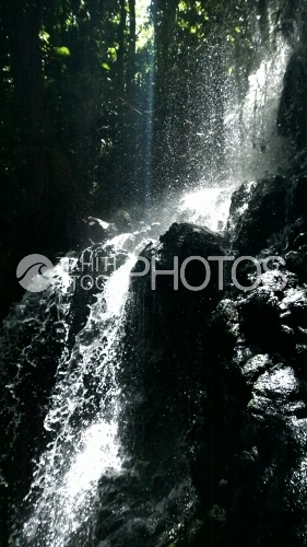 Tahiti, waterfall in the forest, under the sunlight