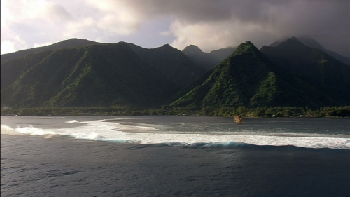 Lateral aerial shot of the pass Teahupo and mountains of Tahiti, in French Polynesia, sunset lighting