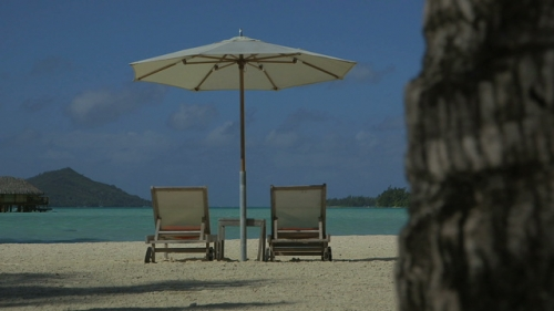 Bora Bora,  Pair of long chairs under big umbrella on the beach