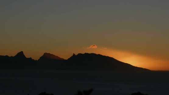 Moorea, very nice and orange sunset behind the mountain chain of the island, shot from Tahiti