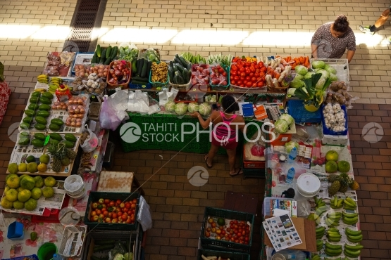 Market of Papeete, lady selling vegetables and fruits on stand