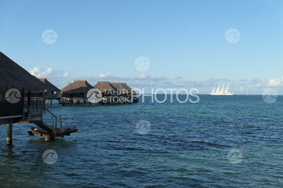 Overwater bungalows in the lagoon, sail boat in the background