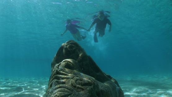 Two snorkelers swimming over Polynesian sculptures layed on the sand in the lagoon, Moorea