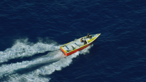 Huahine, aerial view of fishing boat sailing fast on the ocean