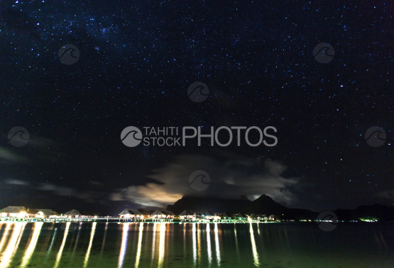 Lagoon of Bora Bora at night under the stars, with lights of hotels