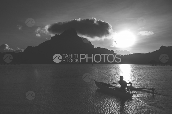Polyneisian on pirogue, paddling on the lagoon of Bora Bora, black and white