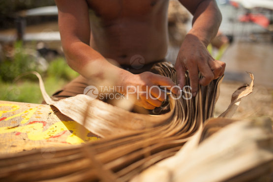 Polynesian working on leaves of pandanus