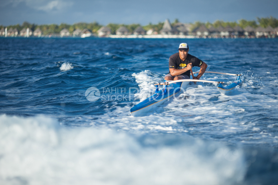 Polynesian paddling on his tahitian canoe on the lagoon of Bora Bora