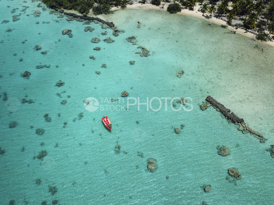 Toau, aerial shot of a red motot boat in the lagoon