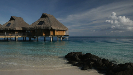 Bora Bora, view on a luxury hotel and bungalow from the white sand beach, slow motion