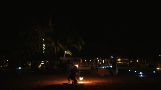 Bora Bora, slow motion shot of fire dancer on white sand by night