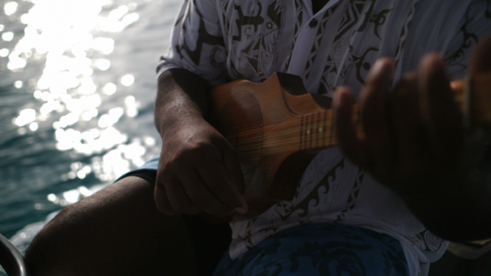 Bora Bora, tahitian musician playing ukulele on the boat, slow motion