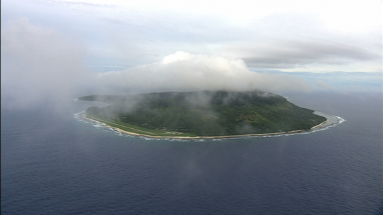 Aerial view of the island  of Rurutu, behind the clouds, austral islands