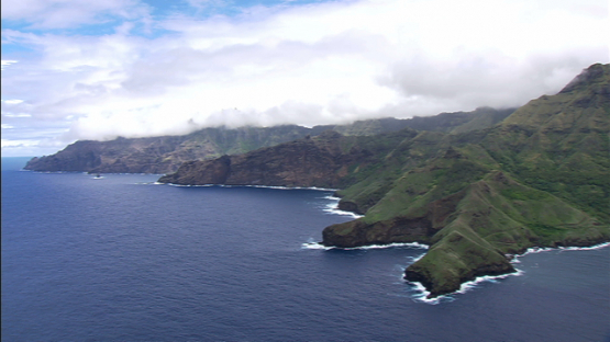 Aerial footage of the rocky coast of Tahuata by the ocean, Marquesas islands