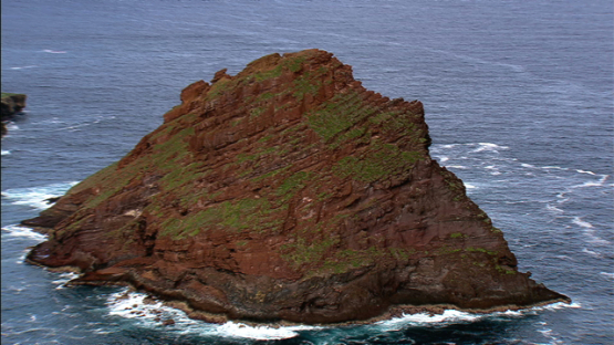 Aerial footage of Ua Huka, Marquesas islands, the red rock in the ocean