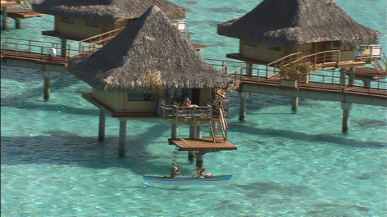 Bora Bora, leeward islands, aerial view of a canoe by overwater bungalows in luxury hotel in the lagoon