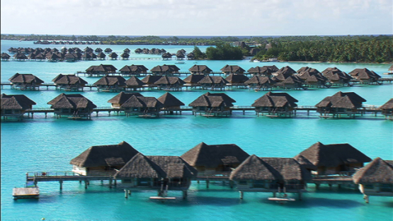 Aerial view of luxury hotels and overwater bungalows in the lagoon of Bora Bora, Leeward islands