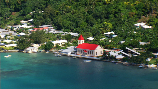 Aerial view of the village of Maupiti, Leeward islands, church beside the lagoon