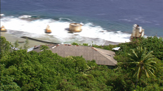 Aerial view of remains of house and pier of Makatea by the sea, Tuamotu islands