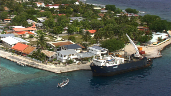 Manihi, aerial view of a cargo ship at the pier of the village Turipaoa, Tuamotu archipelago