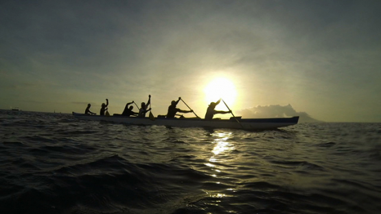 Tahiti, tahitian canoe and paddlers training in the lagoon during the sunset