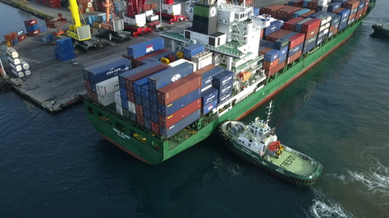 Tahiti, aerial video drone of cargo ship and tug boat in Papeete harbour