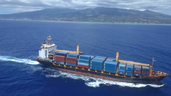 Aerial video by drone of cargo ship cruising by Tahiti, Polynesia