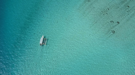 Bora Bora, aerial drone video, above outrigger boat in the lagoon,  leeward islands, Polynesia