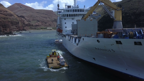 Ua Huka, aerial drone video of anchored cargo ship unloading goods on the barge in the bay, marquesas islands, polynesia, 4K UHD