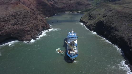 Ua Huka, aerial drone video of cargo cruise ship anchored in the bay, marquesas islands, polynesia, 4K UHD