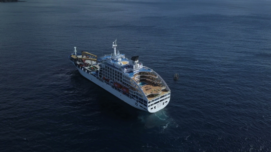 Marquesas islands, aerial drone video of a cruise ship anchored in the bay, Polynesia, 4K UHD