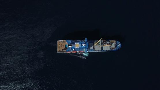 Marquesas islands, aerila drone video above a cruise ship anchored in the bay, Polynesia, 4K UHD