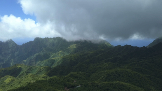 Fatu Hiva, aerial drone video of the mountains, road under heavy clouds, marquesas islands, Polynesia 4K UHD