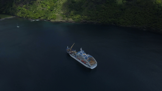 Fatu Hiva, aerial drone video of cruise ship anchored in the Virgins bay, Marquesas islands, Polynesia, 4K UHD
