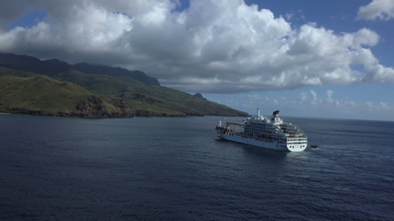 Marquesas islands, aerial drone video of cruise ship anchored in the bay, Polynesia, 4K UHD