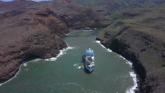 Ua Huka, aerial drone video of cargo cruise ship anchored in the bay, marquesas islands, polynesia, 4K UHD