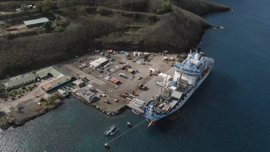 Nuku Hiva, cruise cargo ship discharging containers, Marquesas islands, aerial view by drone 2K7