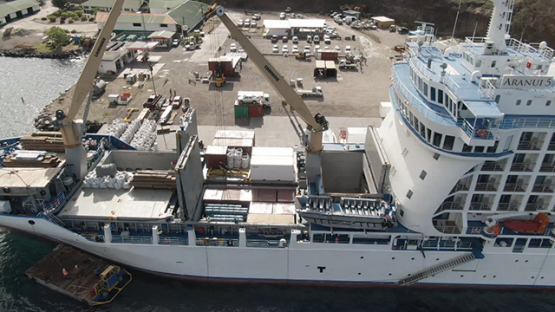 Nuku Hiva, cruise cargo ship discharging containers, Taiohae, Marquesas islands, Polynesia, aerial view by drone 2K7