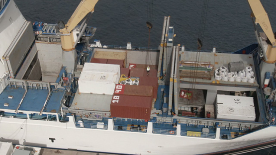 Nuku Hiva, cruise cargo ship discharging containers with crane, Marquesas islands, aerial view by drone 2K7