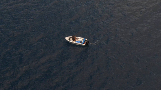 Aerial drone view of Ua Pou, fisher on board of small boat, Marquesas islands, Polynesia, 2K7