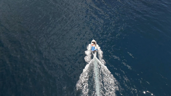 Aerial drone view of Ua Pou, above a motor boat nagating on the ocean, Marquesas islands, Polynesia, 2K7