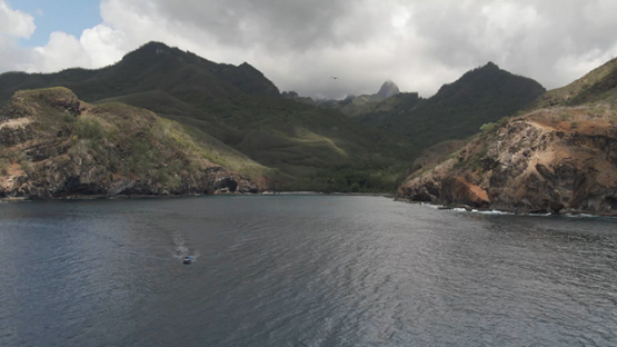 Aerial drone view of Ua Pou and mountains, motor boat by the coast line, Marquesas islands, Polynesia, 2K7