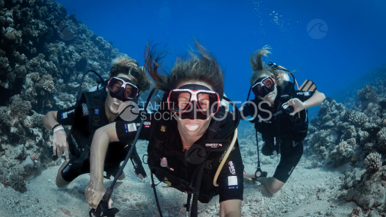 Happy Family diving by the coral reef, Moorea