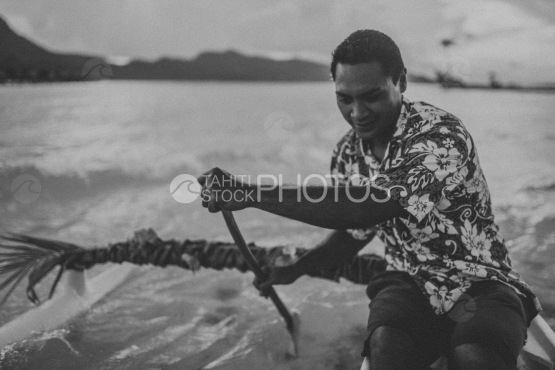 BORA BORA, TRADITIONAL POLYNESIAN man paddling on his  OUTRIGGER canoe