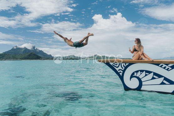 BORA BORA, couple of tourist on outrigger, the husband jumping in the lagoon