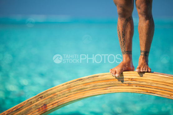 BORA BORA, polynesian standing on TRADITIONAL OUTRIGGER