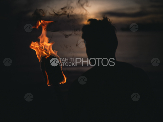 BORA BORA, PORTRAIT OF POLYNESIAN MEN WITH FIRE TORCH AT NIGHT by the lagoon